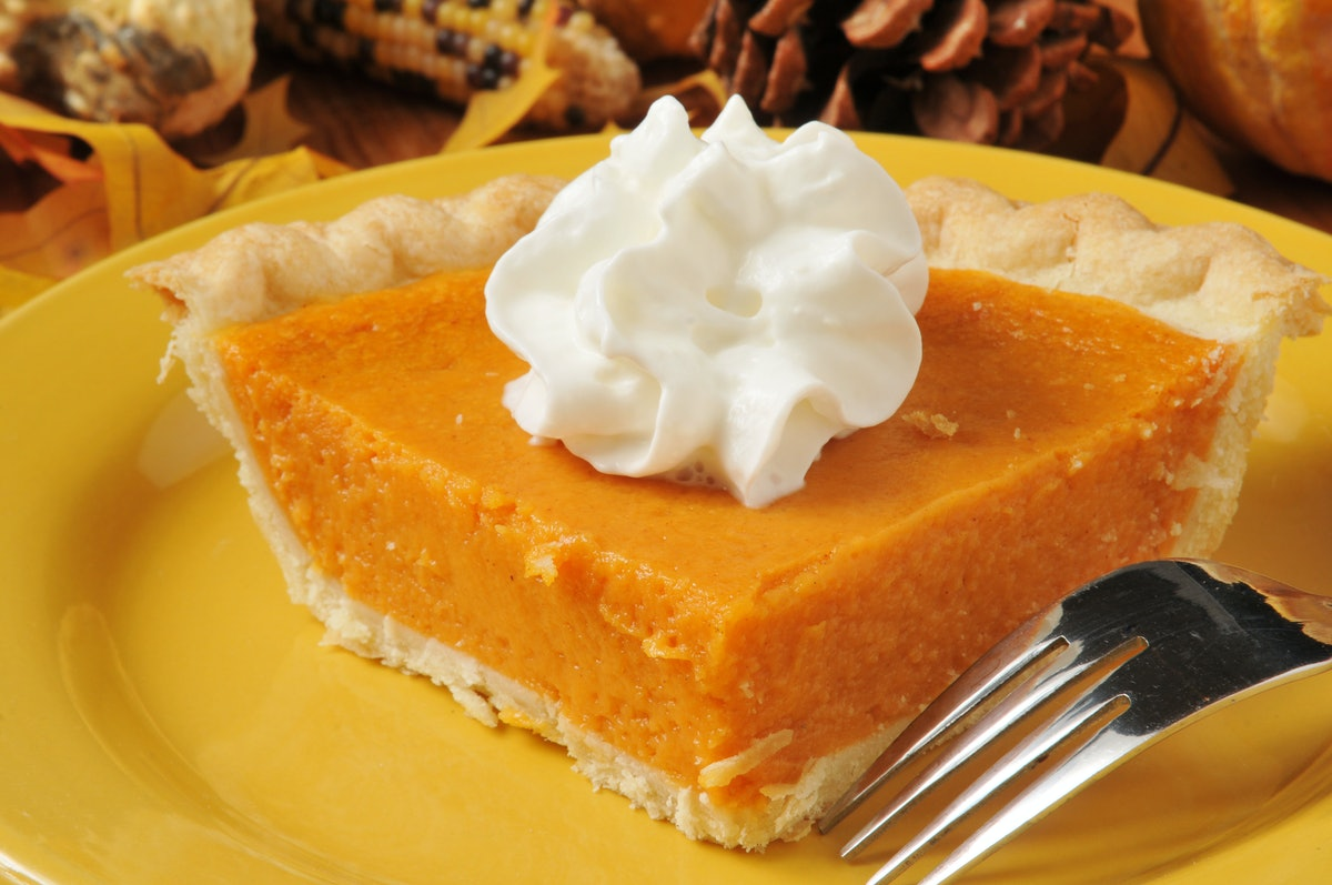 A closeup of a slice of sweet potato pie with whipped cream on top.