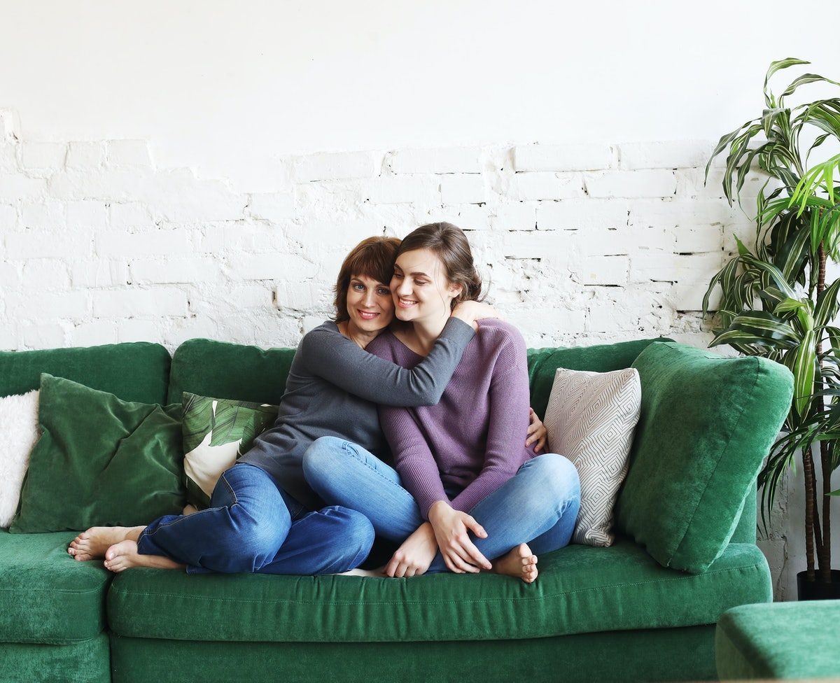 A mother and daughter sit on a green, velvet couch to watch holiday movies.