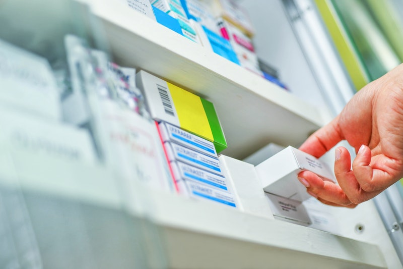Closeup pharmacist hand holding medicine box in pharmacy drugstore. Here's what an expert wants you to know if you're denied medication.