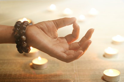 Woman hand yoga and meditation on candle warm glowing background