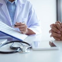 Medical Doctor consultant with patient in clinic office or hospital.
