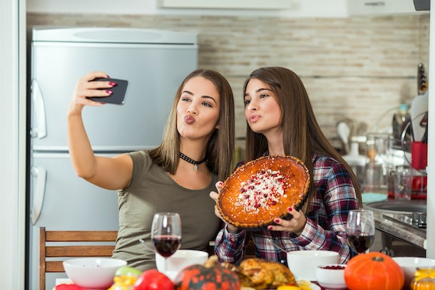 Two brunette girls pose for a selfie with their sweet potato pie on Thanksgiving.
