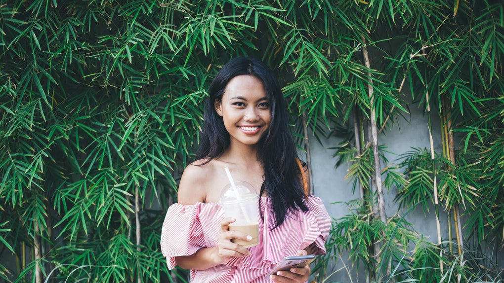Cheerful pretty young Asian woman in pink off-shoulder dress drinking takeaway coffee and texting on smartphone while sitting against wall with green tropical foliage