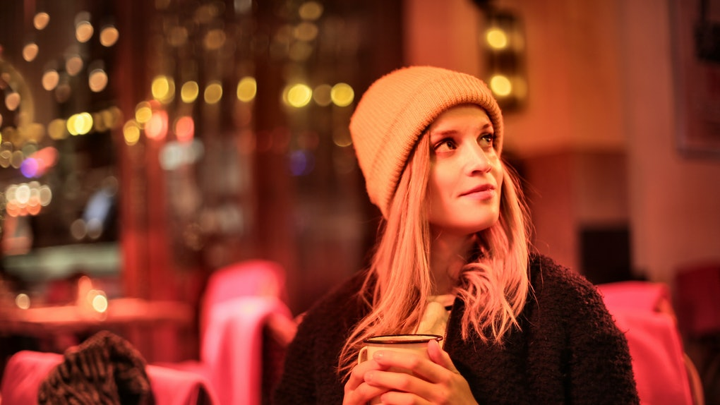 A blonde girl sits in a bar with red lighting in the winter with a holiday drink in her hands.