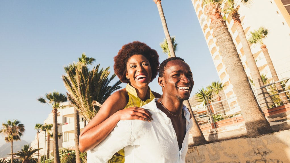 Happy and laugh couple in playful activity together outdoor in tropical place. smiles and joyful concept for black skin race diversity man and woman. Cheerful people in joy outside carrying on back
