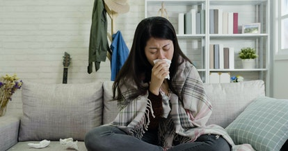 sick woman coughing with tissue in hands cover mouth. illness asian female sneezing running nose using napkin sitting on sofa with trash all round. uncomfortable girl warm with blanket day off.