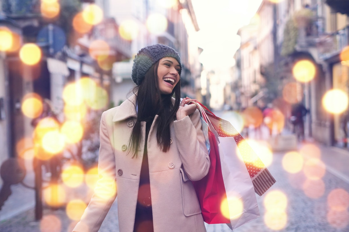 A beautiful girl smiles and is happy while shopping in the stores with sales at Christmas, around th...