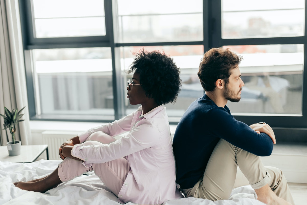 Close-up of an upset interracial couple sitting in bed, back to back, after the quarrel, turning away from each other and looking in different sides.