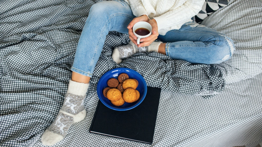 A woman sits on a bed with a blank and white patterned blanket, and eats gingerbread cookies and holds a cup of tea.