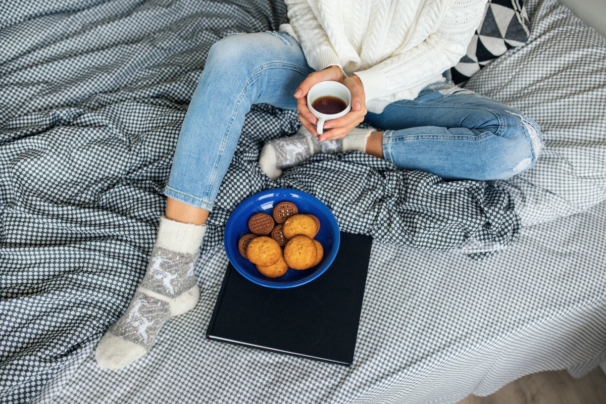 A woman sits on a bed with a blank and white patterned blanket, and eats gingerbread cookies and hol...