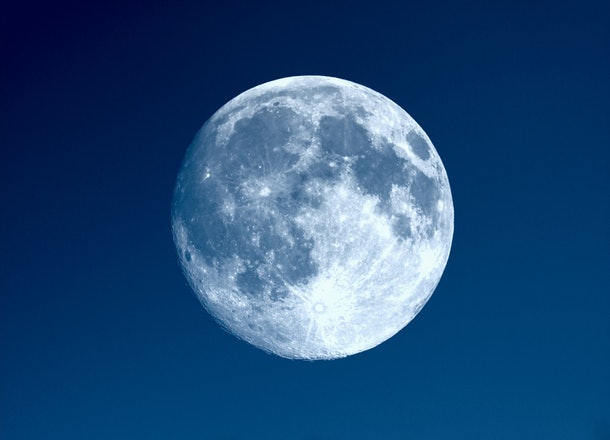 Full moon seen with an astronomical telescope over blue sky