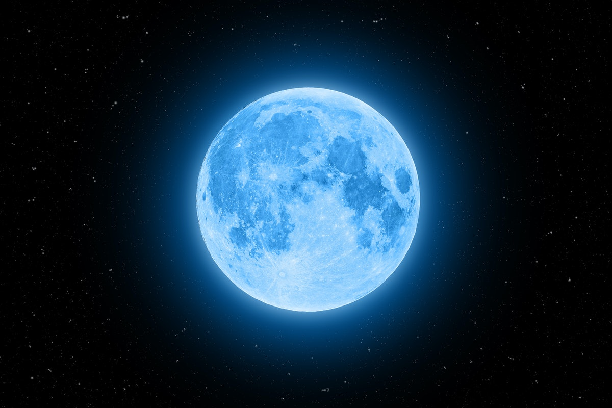 Blue super moon glowing with blue halo surrounded by stars on black sky background