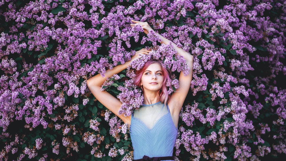 Beautiful girl with pink hair, enjoying the Lilac garden. cheerful teenager walking in the fresh air. soft light style color.
