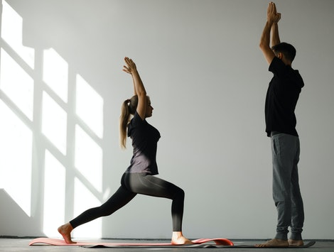 Personal trainer correct his client while doing yoga exercise.