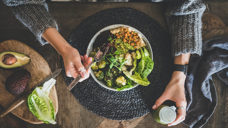 Healthy dinner, lunch setting. Flat-lay of vegan superbowl or Buddha bowl with hummus, vegetable, salad, beans, couscous and avocado, green smoothie and woman's hands over wooden table, top view