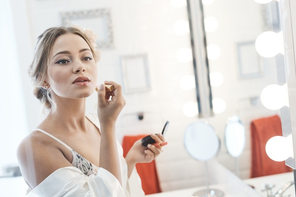 Beautiful young woman applying makeup in bathroom front of mirror.