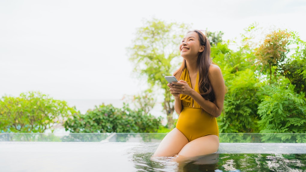 Portrait beautiful young asian woman with cell phone or mobile phone around swimming pool at hotel resort for leisure holiday vacation concept