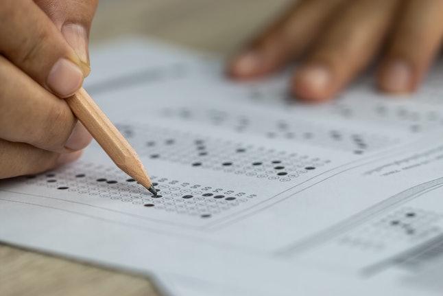 School Students hands taking exams, writing examination holding pencil on optical form of standardiz...