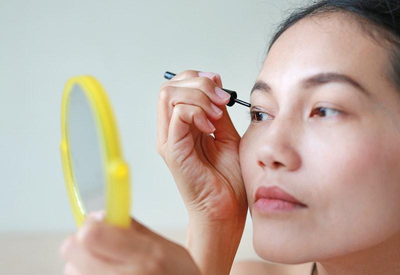 Portrait of beautiful woman making black eyeliner. Beauty Concept.