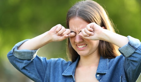 Woman suffering itching scratching eyes outdoors in a park
