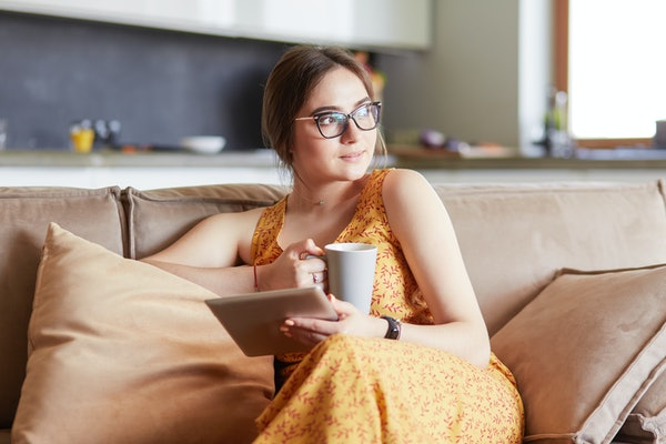 A young woman wearing glasses and a yellow patterned dress uses a tablet while relaxing at home with coffee on the sofa couch.