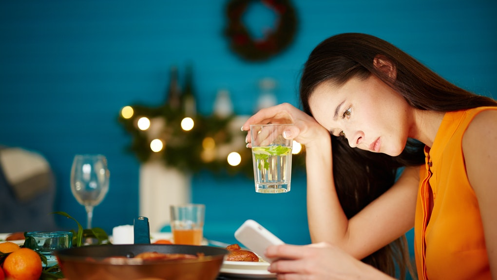Attractive young female sitting alone at table holding glass and using smartphone during dinner party