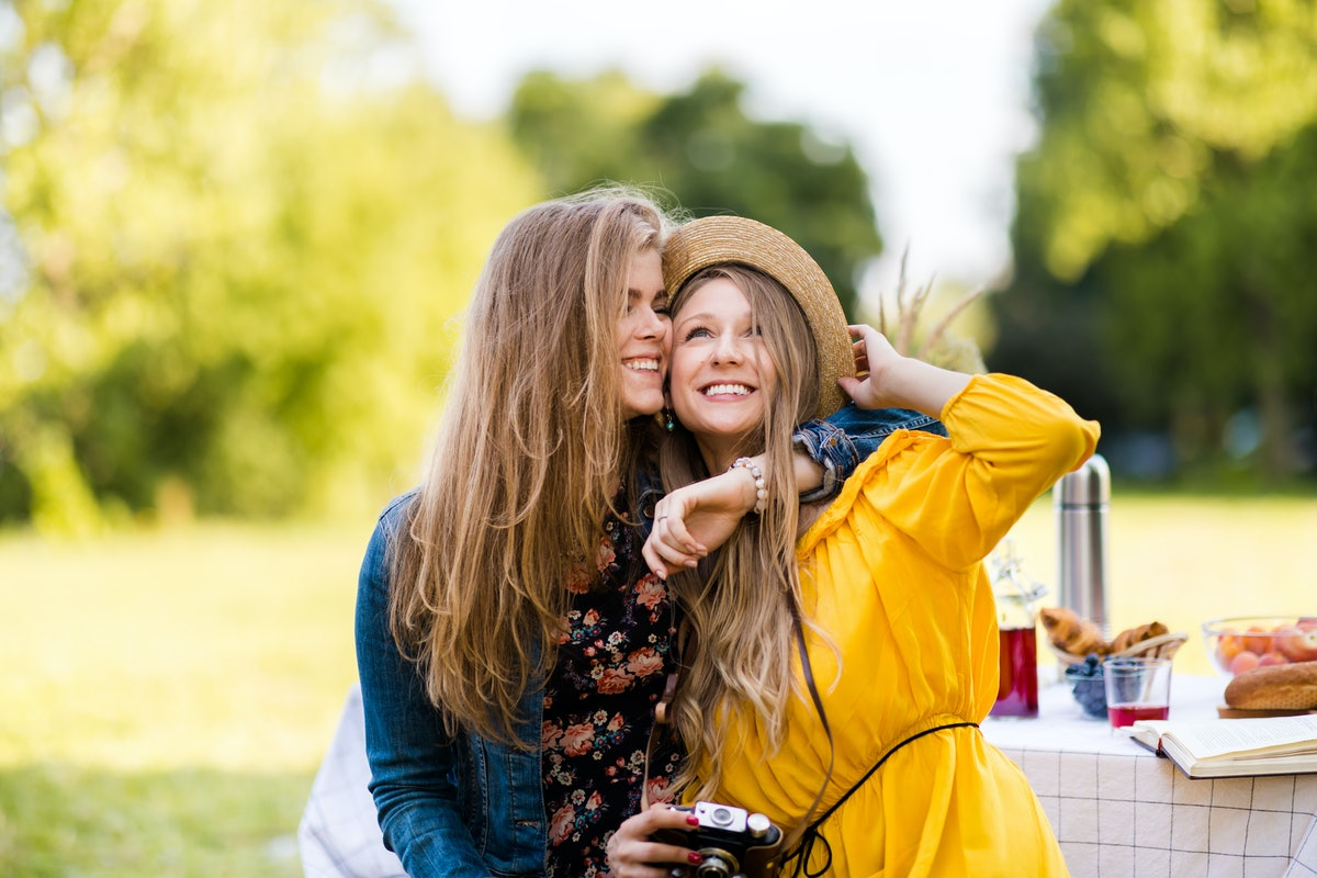 Two girls laugh and one puts her arm around the other on a sunny day outside at a Thanksgiving dinne...