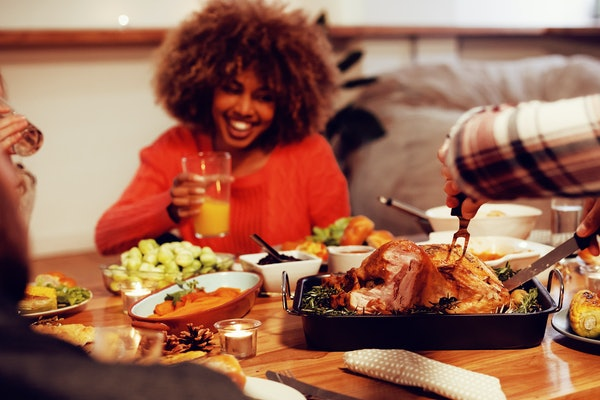 A woman laughs holding a drink in hand while sitting at a Thanksgiving dinner table and the guy across from her carves the turkey.