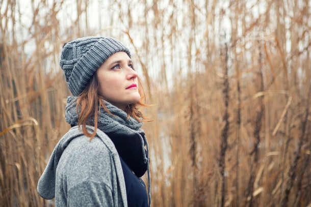 portrait of young woman outdoors in the cold with reeds in the background