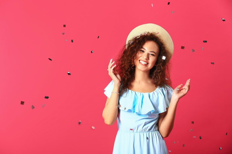 Happy young woman with confetti on color background
