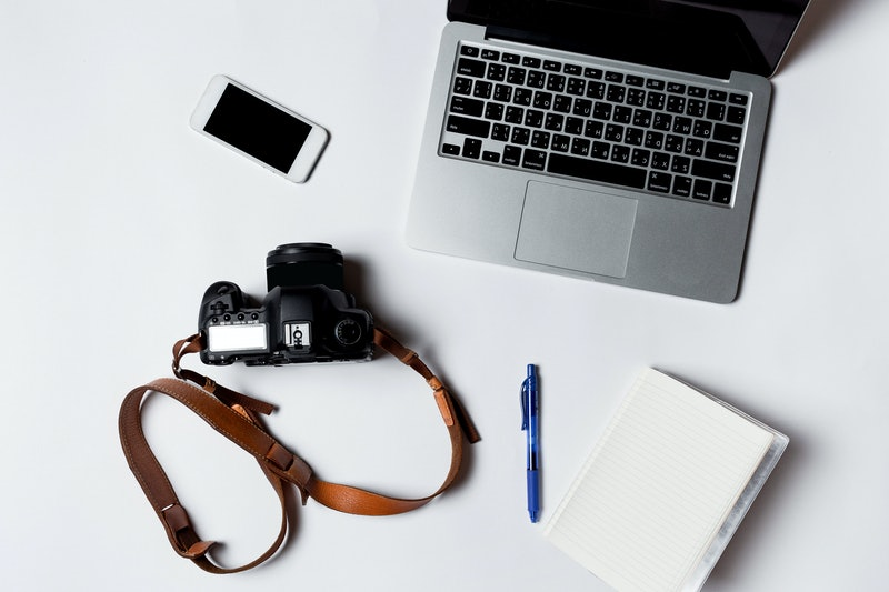 Modern workspace with smartphone, pens, headphone, camera, books and laptop copy space on white color background. Top view. Flat lay style.