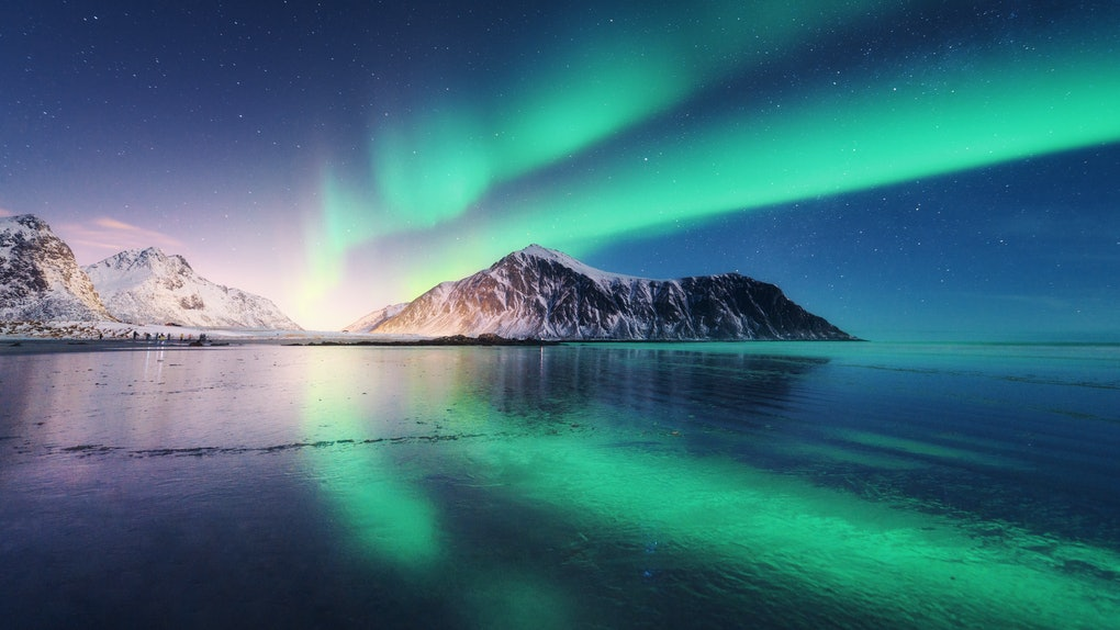 The Northern Lights appear in the night sky over a body of water and small, snowy mountains.