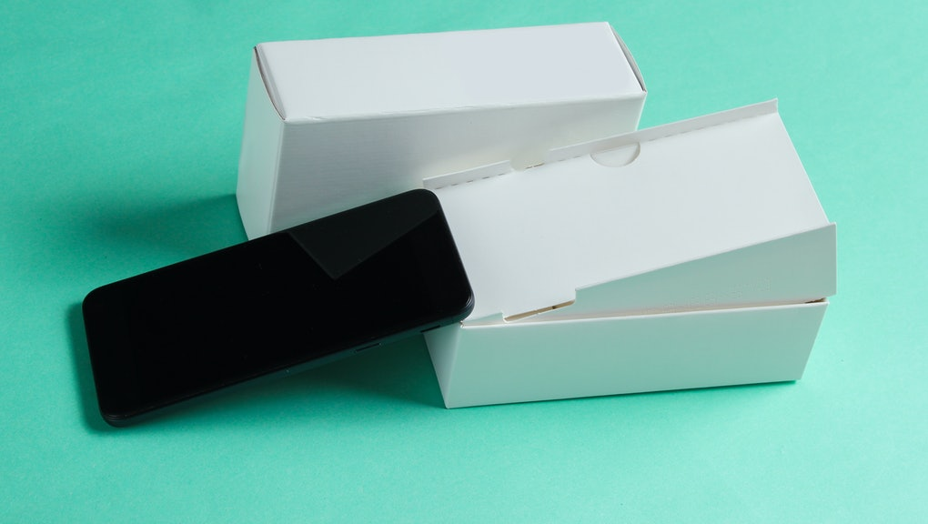 New smartphone with box on blue background. Minimalism concept, unboxing