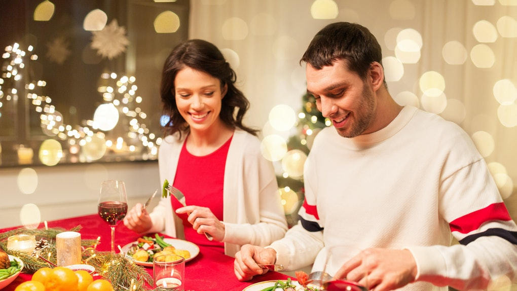 A happy couple enjoys a holiday dinner at home sitting side by side.