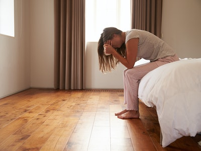 Woman Suffering From morning sickness Sitting On Bed And Crying