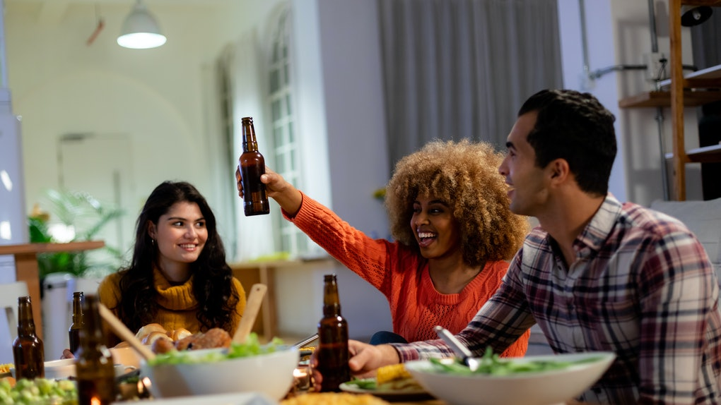 A group of friends enjoying a Thanksgiving dinner and beer in a kitchen,