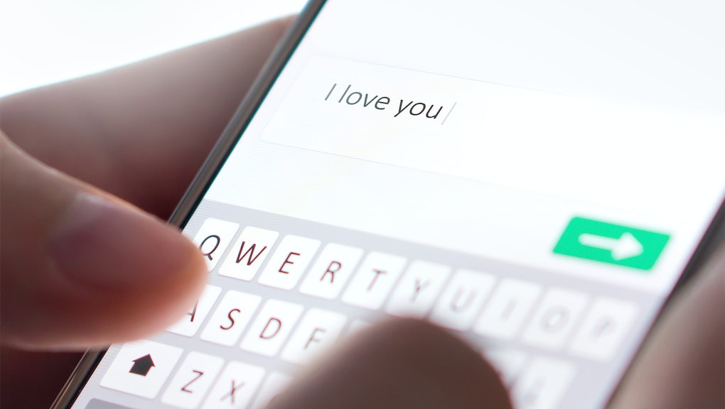 Sending I love you text message with mobile phone. Online dating, texting or catfishing concept. Rom...