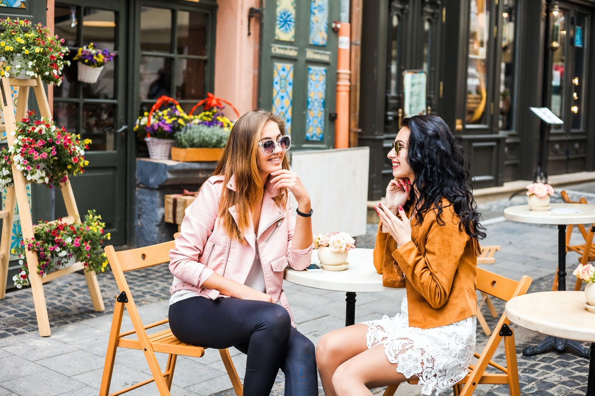 Two stylish friends sit at an outdoor restaurant in the city for Thanksgiving brunch.