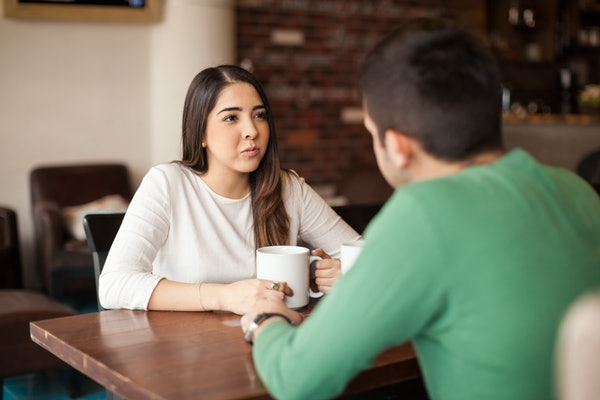 Cute young brunette drinking some coffee while talking with a male friend at a cafe