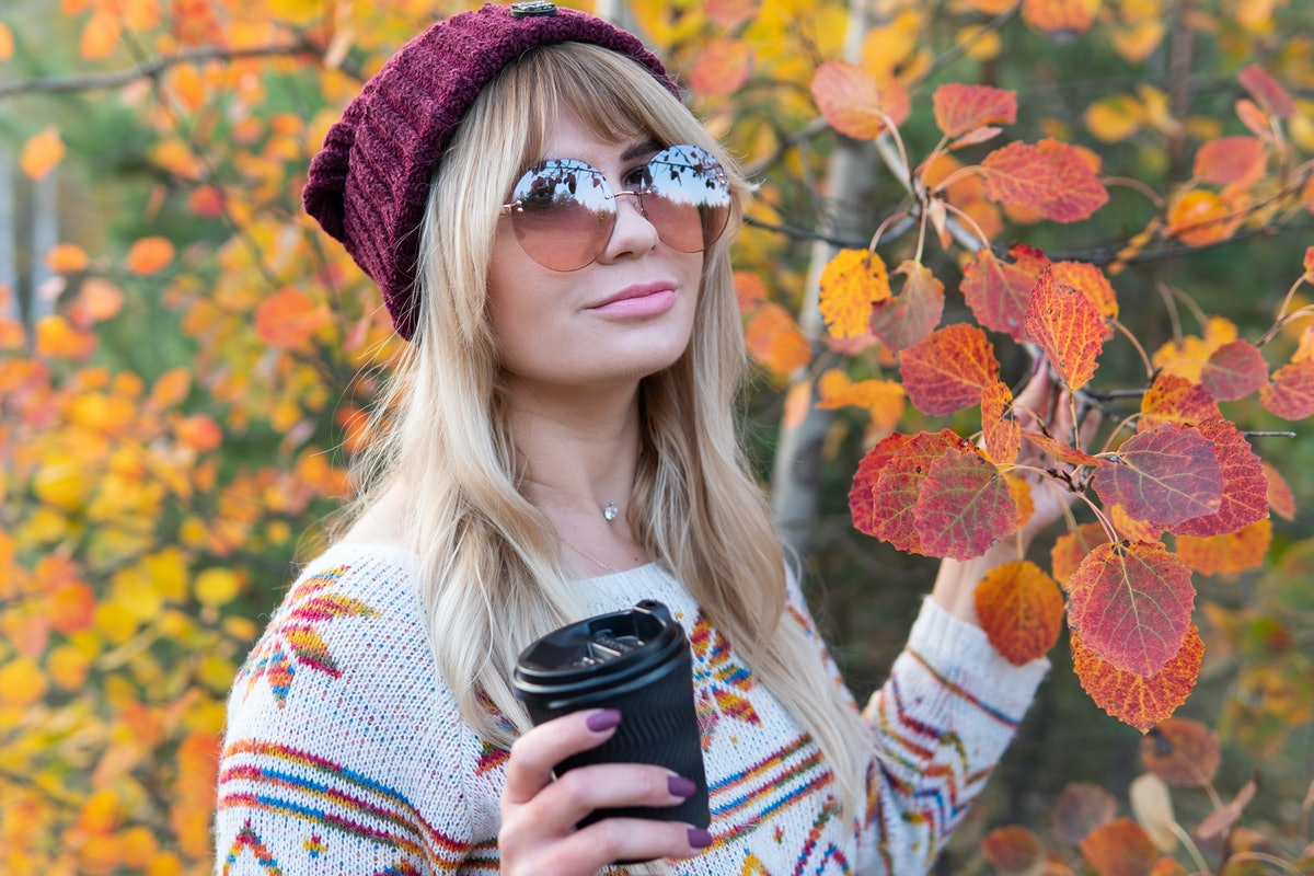 A blonde woman with sunglasses, a colorful sweater, and beanie holds a coffee cup, standing next to leaves in the park on a fall morning.
