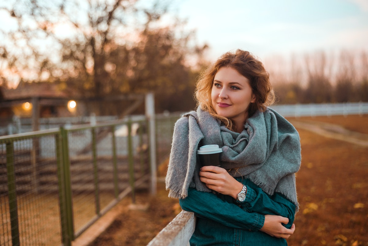A smiling woman wearing a scarf warms up with a cup of coffee on a crisp fall morning.