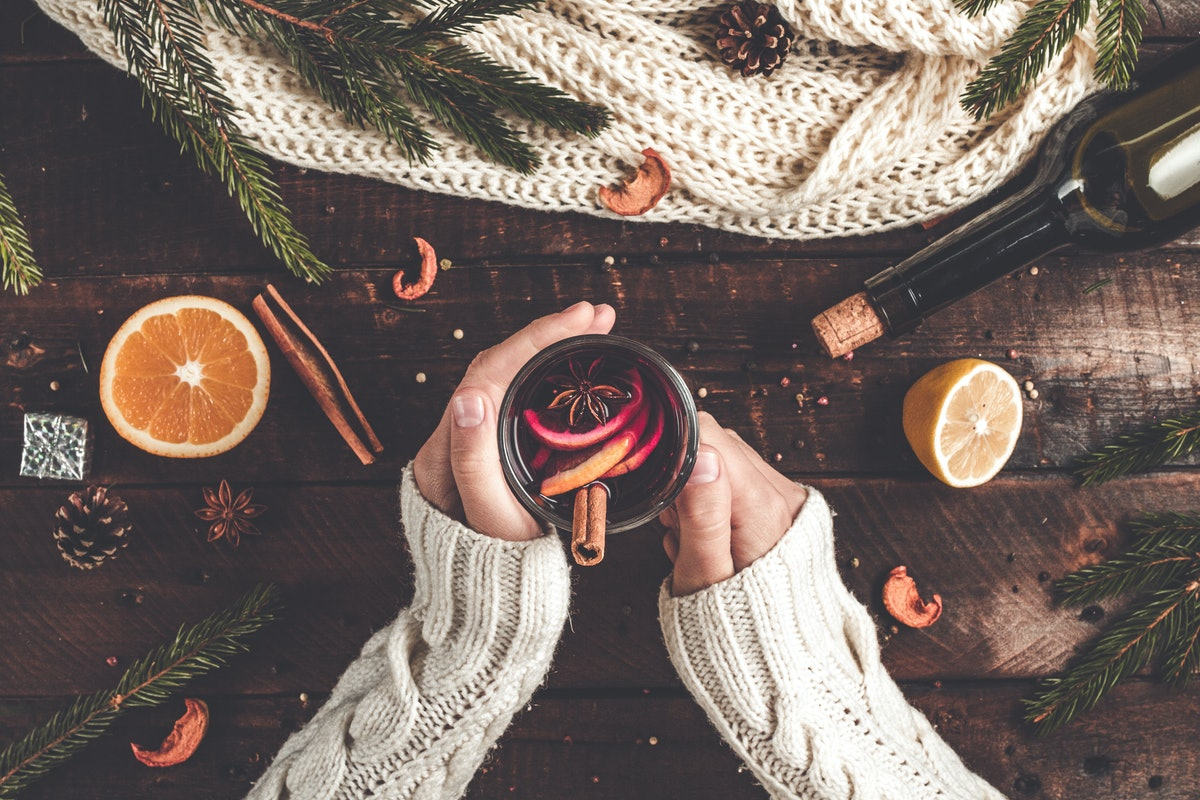 A woman's hands hold a mug of mulled wine on a table with winter decor.