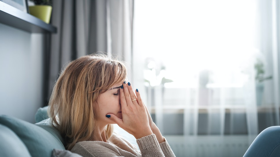 Sad woman sitting on sofa at home, thinking about important things