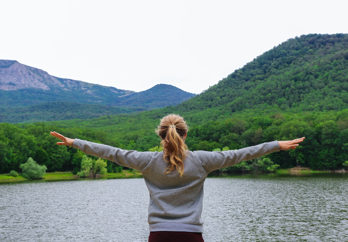 A bright girl with her arms spread apart is standing against the backdrop of mountains and a lake, ...