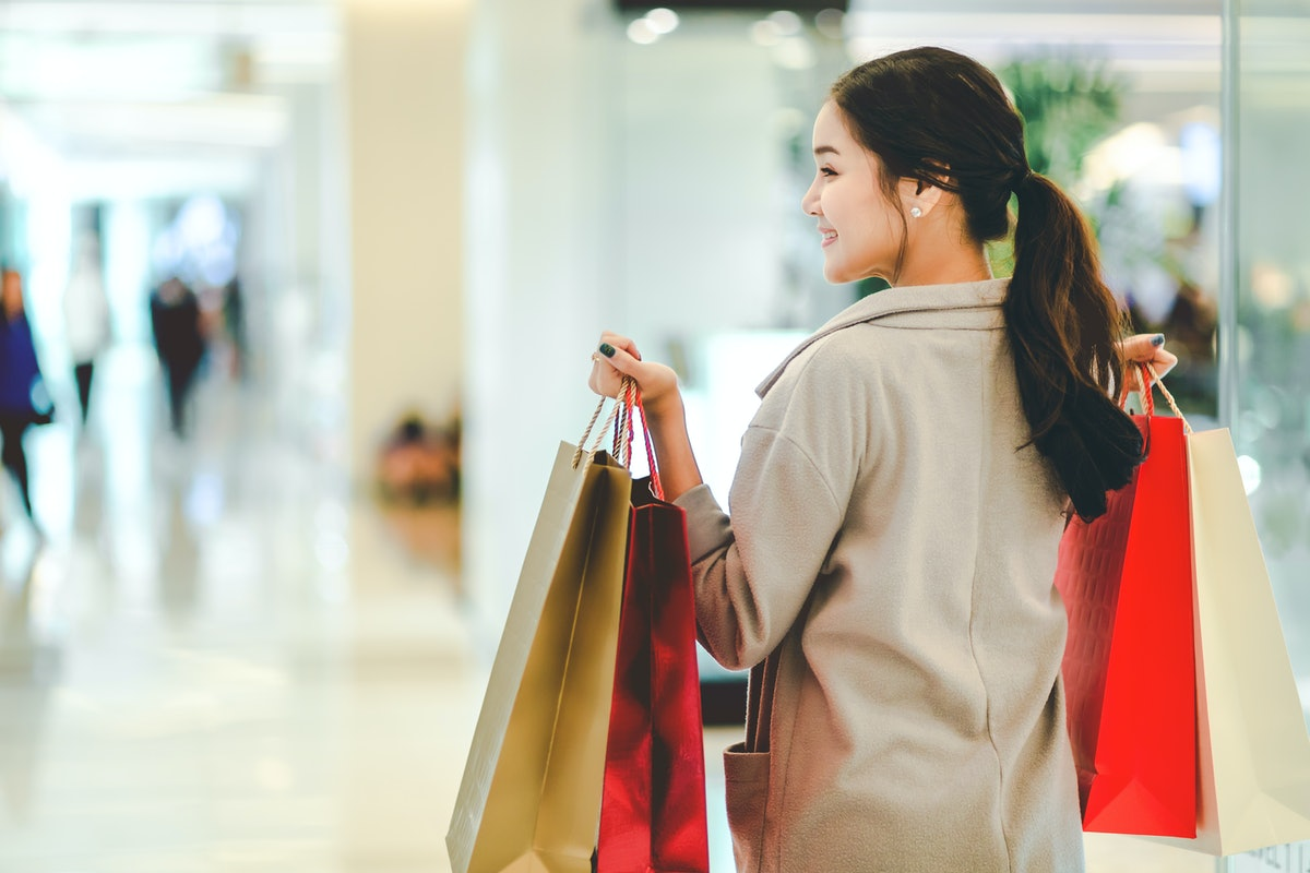 Lifestyle shopping concept, Young happy asian woman with paper bag and coat in shopping mall, vintag...