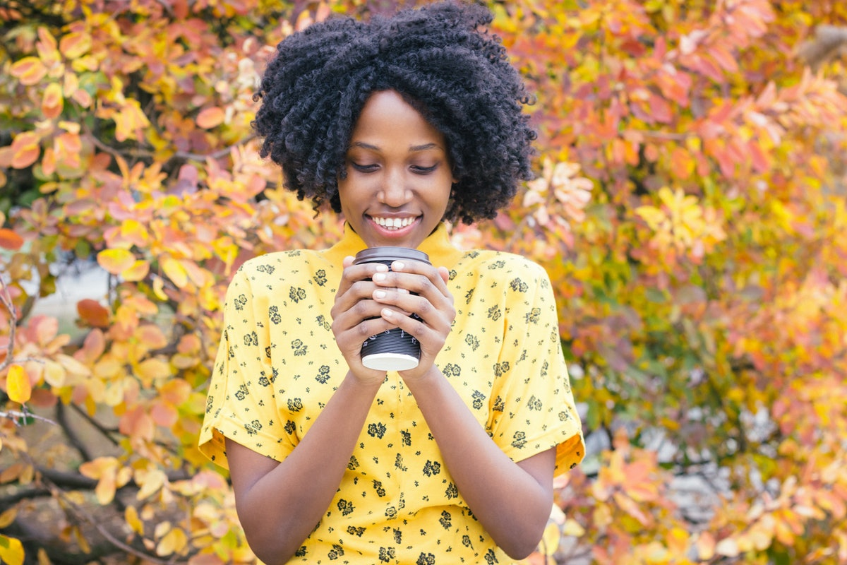 A woman in a yellow T-shirt smiles and looks down at her cup of coffee with yellow foliage in the background on a fall morning.