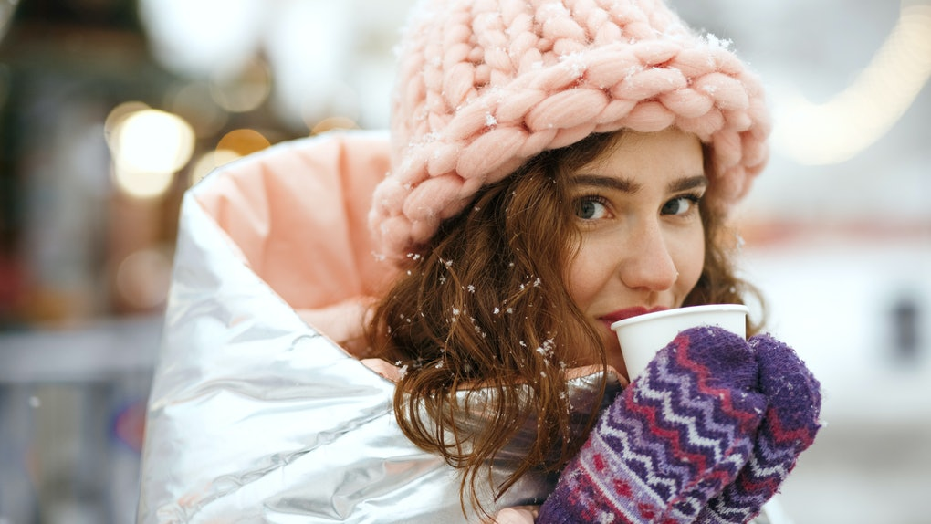 A woman in a metallic coat, pastel pink hat, and purple mittens sips mulled wine at a holiday market.