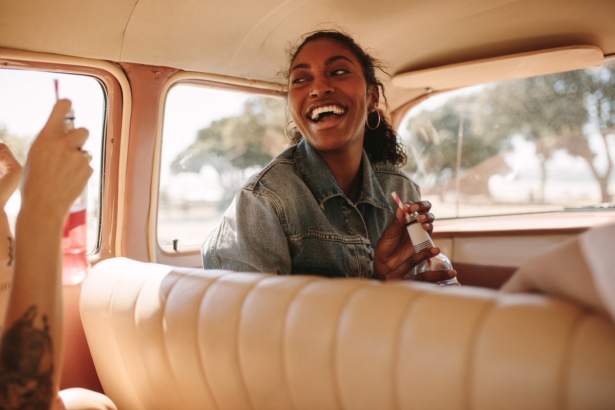A woman laughs in a car while on a road trip with her friends.