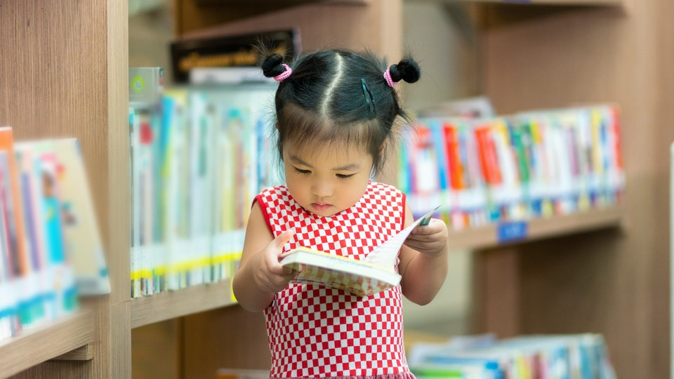 A little girl reading a book in a bookstore