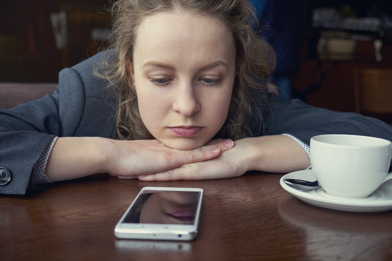 Disappointed sad woman looking at phone and waiting message or call